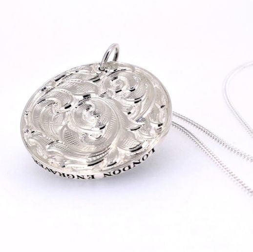 Sterling silver pendant hand engraved with a scroll patternwork